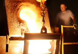 Foundry employee pours molten iron into mold for casting.