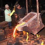 Clarksville Foundry employees pour molten iron into a series of molds.