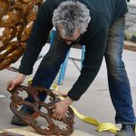Sculptor Vaughn Randall assembles individual castings into the spherical sculpture, spanning 8 feet in diameter, at Downtown Commons.