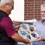 "Robert Lueck, a former First Presbyterian Church pastor, accepts a replica casting from Clarksville Foundry President Charles Foust Jr. Lueck submitted the winning name for ""Window to the World,"" the spherical sculpture in Downtown Commons created in a partnership between Clarksville Foundry and sculptor Vaughn Randall."